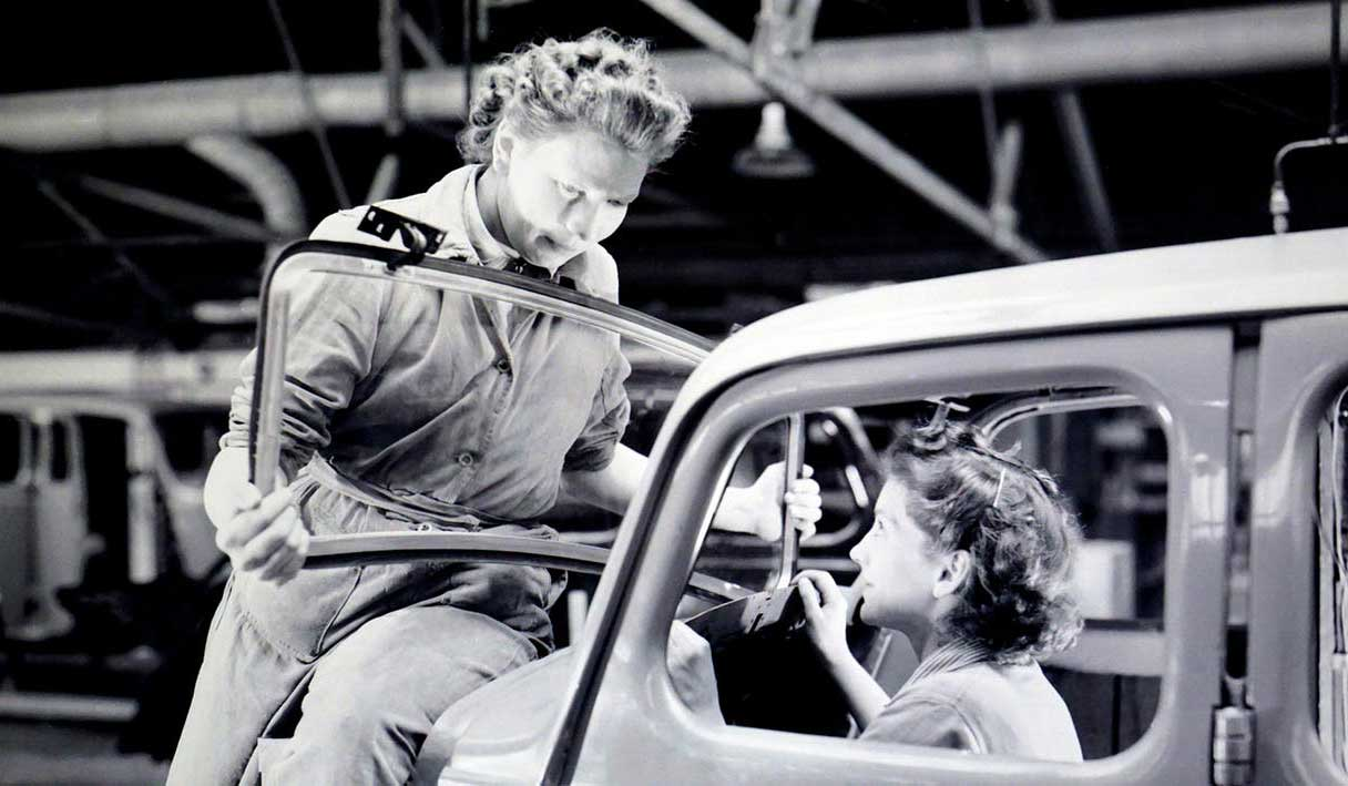 Old photo showing two ladies fitting automobile glass
