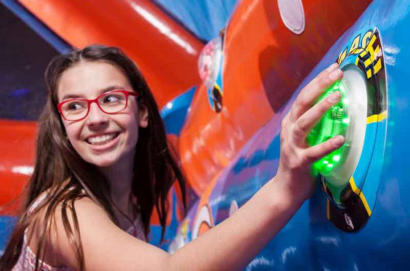 Girl on bouncy castle hits a button on an interactive panel